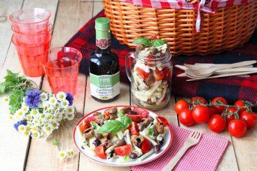Insalata di pasta con pomodori, olive e bocconcini di maiale